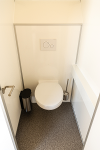 Großzügige WC-Kabinen mit Toilettenpapierhalter, Toilettenbürste und Hygienemülleimer